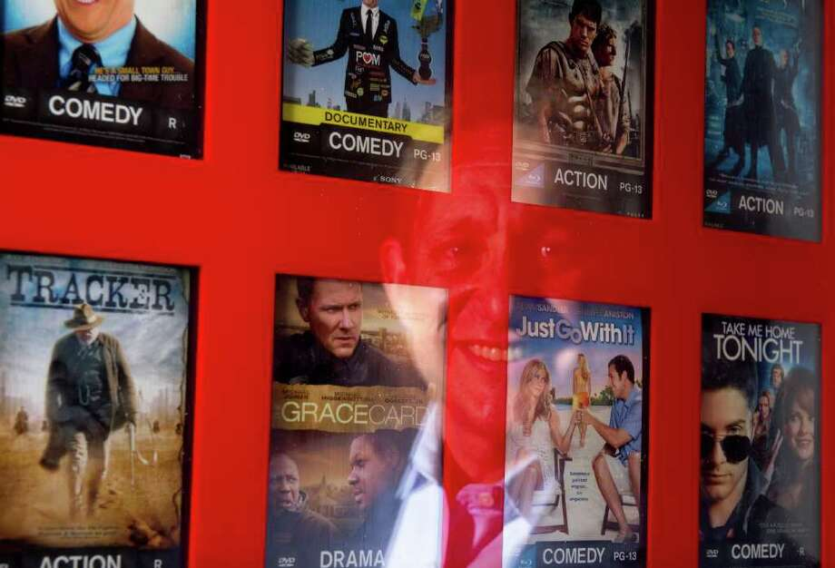 In this photo taken Aug. 26, 2011, Gary Cohen, senior vice president of marketing and customer experience at Redbox, is reflected in one of the kiosks  at the company's offices in Oakbrook Terrace, Ill. Redbox is looking to pick up new customers with rival Netflix poised to raise its prices by as much as 60 percent for its existing subscribers beginning Sept. 1. (AP Photo/Brian Kersey) Photo: Brian Kersey, FRE / FR84753 AP