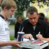 """Actor Ray Liotta takes a break from filming on set of the movie """"The Place Beyond the Pines"""" to greet some eager fans waiting on Story Avenue in Niskayuna, N.Y. on Wednesday, Aug. 31, 2011. Here Ted Dalakos has the actor sign an autograph as he comes home from picking up a pizza.  (Lori Van Buren / Times Union archive)"""