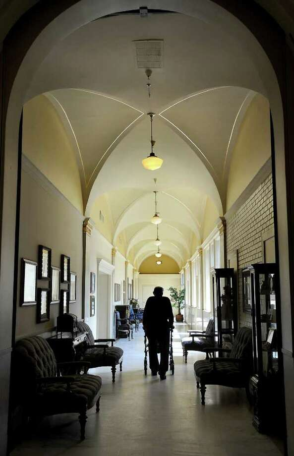 A resident of the Hotel Beaumont walks down the hall in Beaumont, Wednesday. The Hotel Beaumont will be closing and relocating residents to other facilities. Tammy McKinley/The Enterprise Photo: TAMMY MCKINLEY