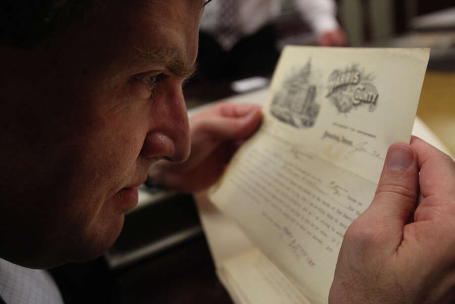 Bill Kroger, chairman of the Texas Court Records Preservation Task Force, examines a document from 1910 at the Harris County Civil Courthouse. Photo: Mayra Beltran/mayra.beltran@chron.com / © 2011 Houston Chronicle