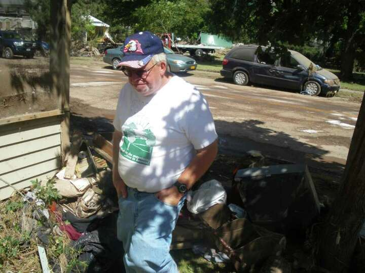 Richard Morse walks through the yard of his home in Prattsville, destroyed  by flooding of the Scho