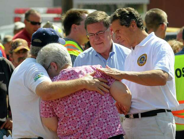 New York Gov. Andrew Cuomo, Right, with state Sen. James Seward, second from right, comforts Ricard and Emily Morse while surveying the damage caused by Tropical Storm Irene in Prattsville, N.Y., Wednesday, Aug. 31, 2011. Tropical Storm Irene put a $1 billion whipping on New York, most of it upstate where heavy rains spawned flash floods that shredded roads, washed out bridges and knocked buildings from their foundations, Cuomo said Wednesday.   (AP Photo/Hans Pennink) Photo: Hans Pennink