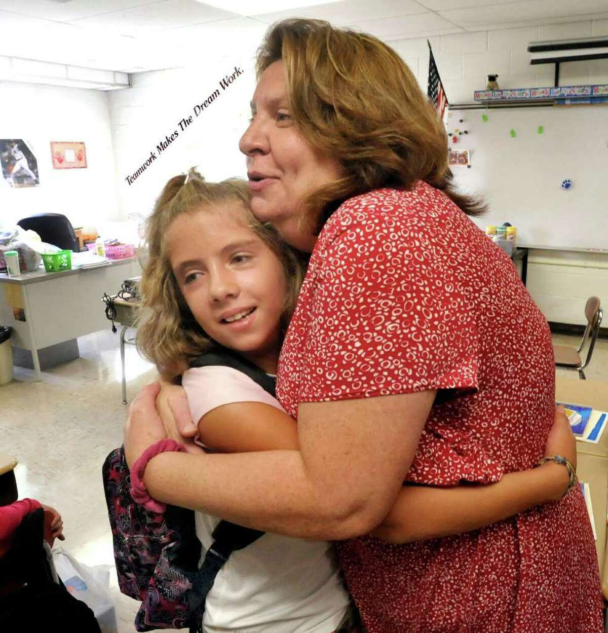 Katya LaPierre gets a welcoming hug from Kathleen Quader, her fourth-grade teacher, on the first day of school at the Ralph M. Johnson Elementary School in Bethel Thursday, Sept. 1, 2011.