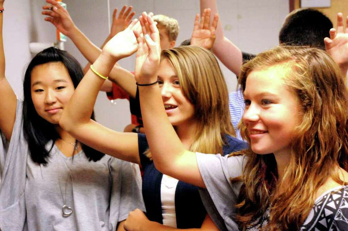 Freshmen Kari Kavall, left, Morgan Veilleux, center, and Molly Barnum answer questions in health class on the first day of school at Bethel High School Thursday, Sept. 1, 2011.