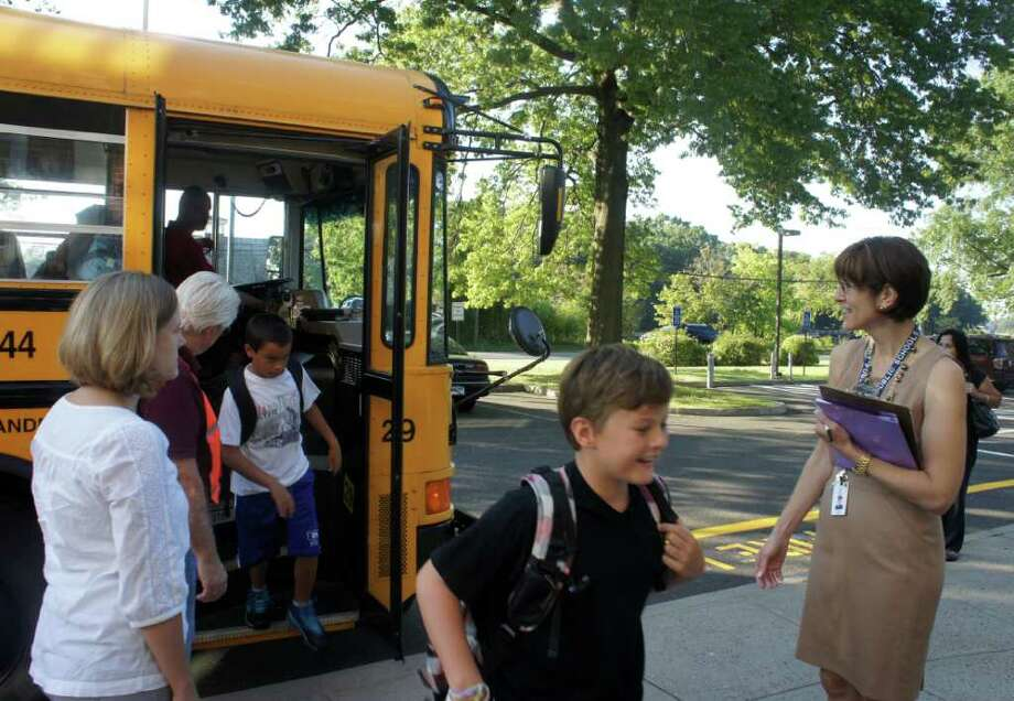 Saugatuck Elementary School Principal Julie Droller, right, greets students as they arrive for the first day of classes on Thursday, Sept. 1, 2011. Photo: Paul Schott / Westport News