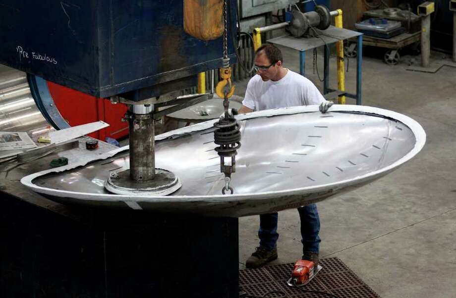 In this Aug. 30, 2011 photo, Larry Chappell uses a ?C Press? machine to form a tank head at JV Northwest, in Canby, Ore. JV Northwest manufactures stainless steel vessels. Manufacturing growth slowed slightly in August, but the sector expanded for the 25th straight month, easing fears the economy is on the verge of another recession. (AP Photo/Rick Bowmer) Photo: Rick Bowmer, STF / AP