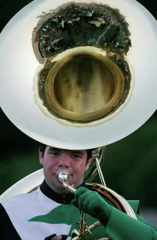 "With the crowd refracted in the sheen of his tuba, Peter O'Connor, a Norwalk High School Marching Band member performs during ""Spirit Night"" at Andrews Field in Norwalk on Friday Aug. 26, 2011. The band and color guard kicked off the new school year with performances by dozens of its members. Photo: J. Gregory Raymond / Stamford Advocate Freelance"