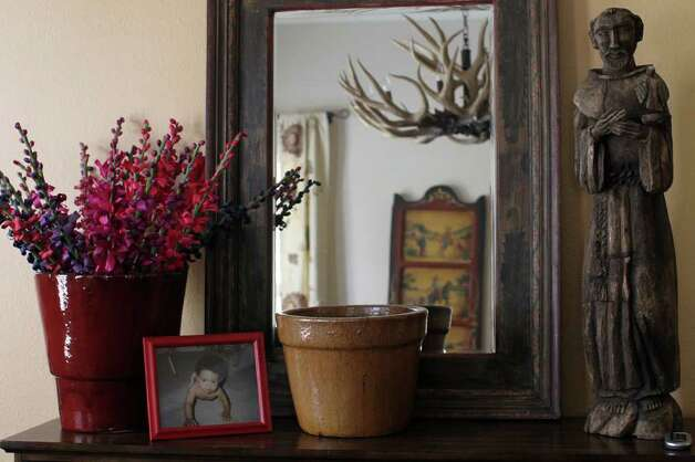 A side table in the dining room displays a photo of the Salenga's daughter, Daniella, and a St. Francis statue that was a gift from Christine's sister. Photo: Jennifer Whitney, Special To The Express-News / special to the Express-News
