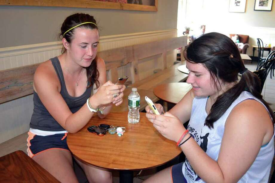 Katelyn Kean, 17, of Newtown and her sister Haley Kean, 14, visited Starbucks on Church Hill Road in Newtown Thursday afternoon to check Facebook and emails. Their home has not had electricity since Sunday. Photo: Stacy Davis