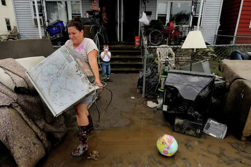 Mandy Adams carries a flood damaged refrigirator out of her Front Street home to place curbside d