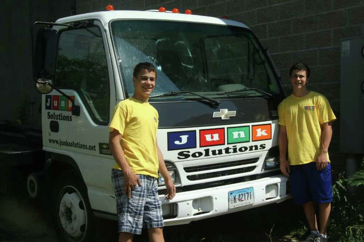 Nicholas D'Elia, left, and his brother, Anthony, were the first employees of Junk Solutions, which their parents Susan and Michael D'Elia, co-owners of Olympic Construction, started this summer as another unit of the Stamford business.