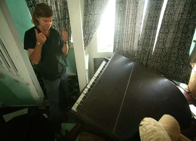 Edward McGann looks at his piano that fell through the floor of his living room at 25 Point Beach Drive in Milford. Waves and the storm surge from Hurricane Irene blasted through the south facing exterior wall of the home, tore up floors, and damaged the house's foundation. Photo: Brian A. Pounds / Connecticut Post