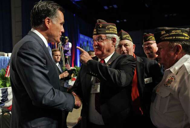 Presidential candidate Mitt Romney, left, is greeted by Joseph N. Stavolta of Massachusetts, center, and other veterans after Romney addressed the veterans at the VFW National Convention at the Convention Center, Tuesday, August 30, 2011. Photo: Bob Owen/rowen@express-news.net