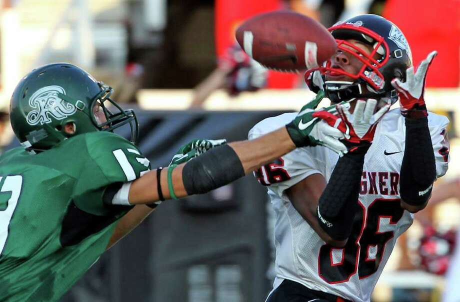 Wagner receiver Xavier LaGrant catches a long pass in the first quarter despite pressure from defender Ty Branch as Reagan plays Wagner at Comalander Stadium  on August 27, 2011. Photo: Tom Reel/treel@express-news.net
