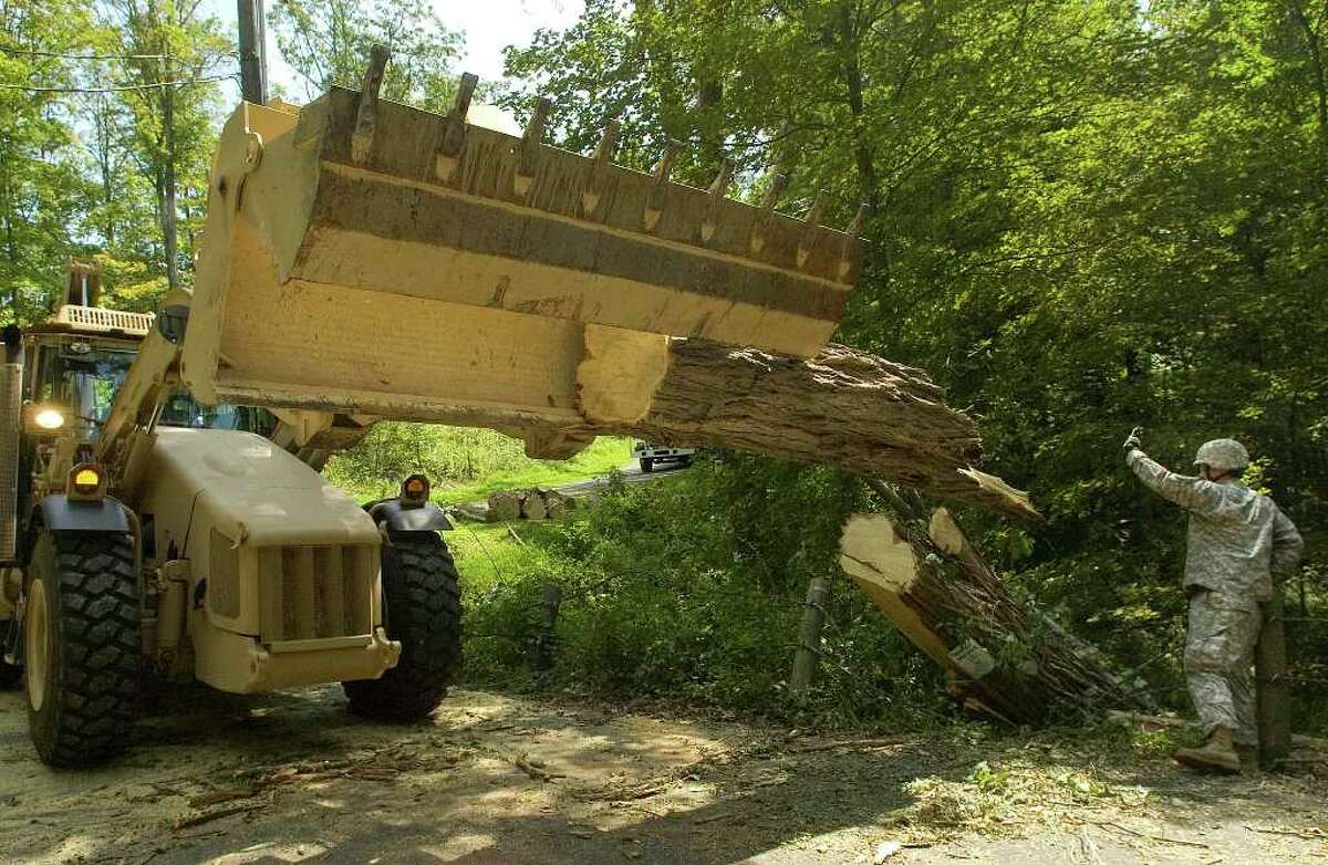 Army National Guard Staff Sgt. Gregory Gallagher, right, guides an improved high mobility engineer excavator in the removal of a section of tree along Topstone Road in Ridgefield on Thursday, Sept. 1, 2011.