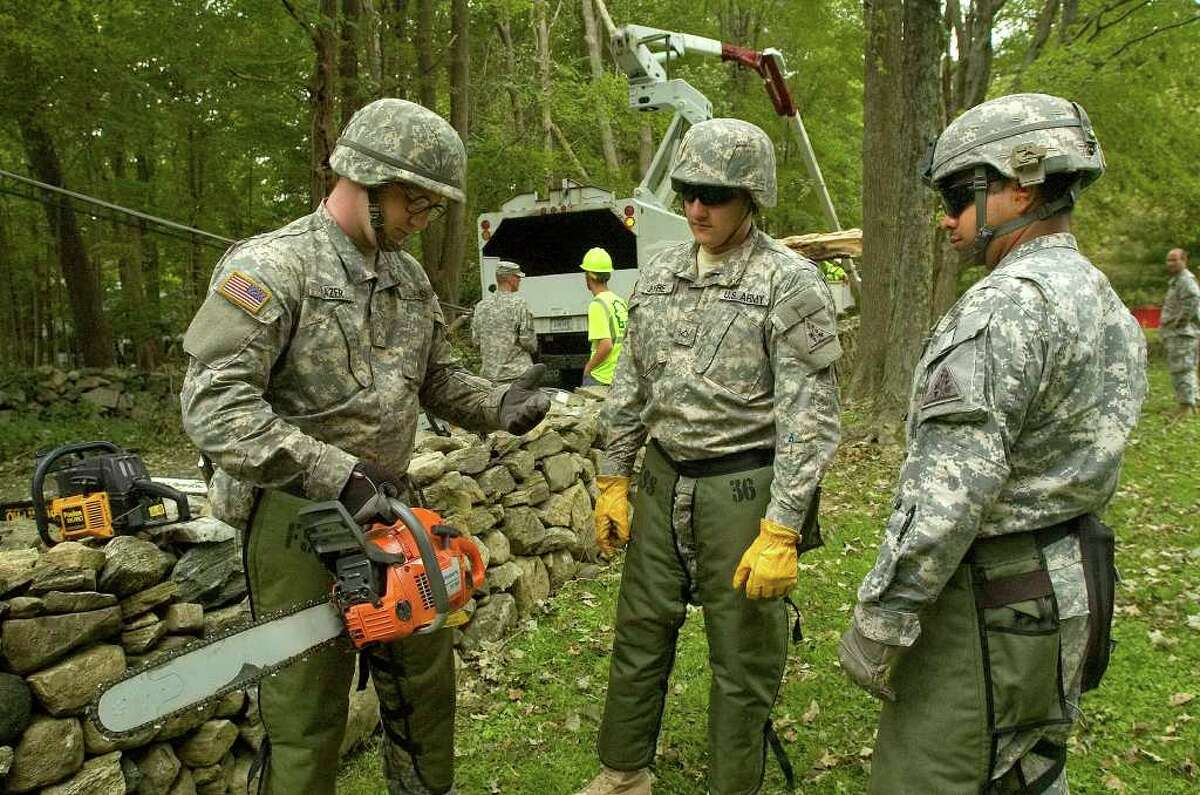 Army National Guards Pvt. Michael Frazer, left, gives Pfc. Rodolfo Jofre, center, a refresher course on the usage of a chainsaw as Staff Sgt. Jose Osorio watches during cleanup efforts along Fire Hill Road in Ridgefield on Thursday, Sept. 1, 2011.