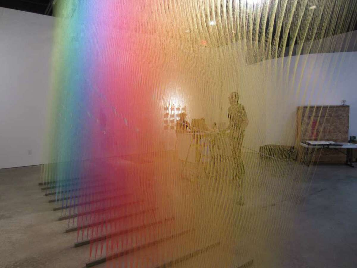 Gabriel Dawe works on installing a sculpture consisting of thousands of yards of thread at Peel Gallery.