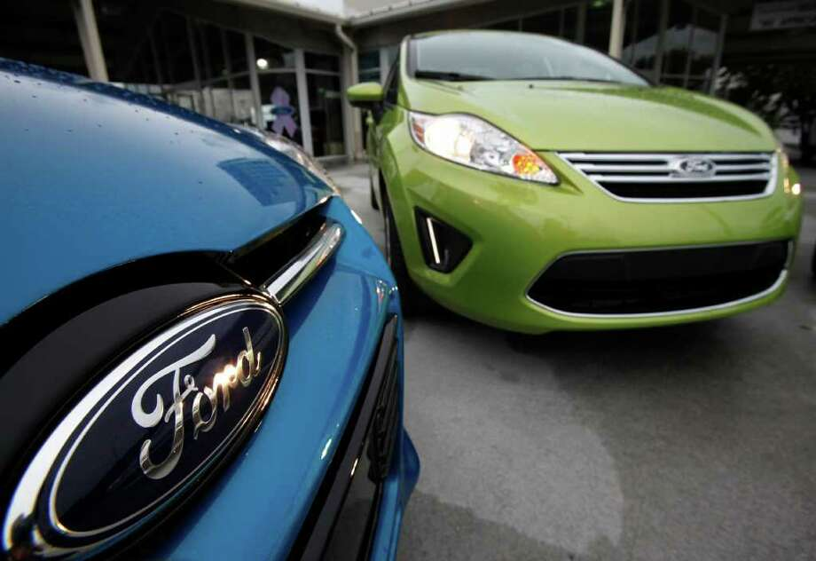 In this Aug. 31, 2011 photo, a Blue Candy Metallic 2012 Ford Focus SEL Sedan, left, and a Lime Squeeze Metallic 2012 Ford Fiesta SE  are dispayed at the Maroone Ford of Miami dealership in Miami. Ford was one of several automakers who surprised the industry Thursday, Sept. 1, with double-digit sales increases. General Motors? August sales were up 18 percent, while Nissan?s rose 19 percent. (AP Photo/Wilfredo Lee) Photo: Wilfredo Lee, STF / AP