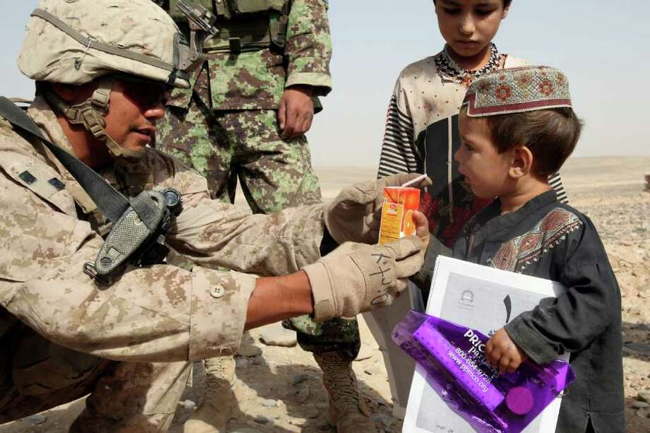 """Cpl. Henry Garza, of the Lone Star Battalion and a native of Halletsville, offers juice to an Afghan child. """"I grew up in the country,"""" said Garza. """"In the summertime where I'm from, the kids just try to occupy themselves outdoors like these kids do."""" Photo: Staff Sgt. Jeremy Ross, Regional Command Southwest"""