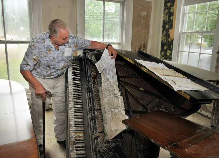 Ed August inspects the flood damage to his concert grand piano in the salon of his Wedgewwood bed an