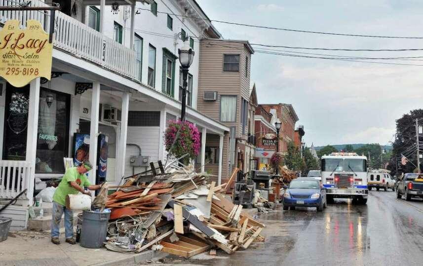 Russell Van Allen, left, piles storm debris on the sidewalk on Main Street in the Village of Schohar
