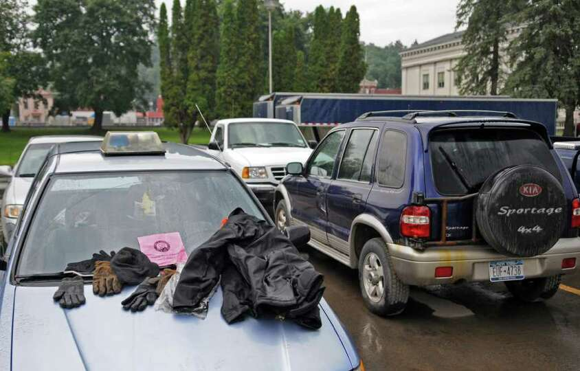 Gloves and a jacket are laid on the windshield of a car to dry, despite a light rain falling, outsid