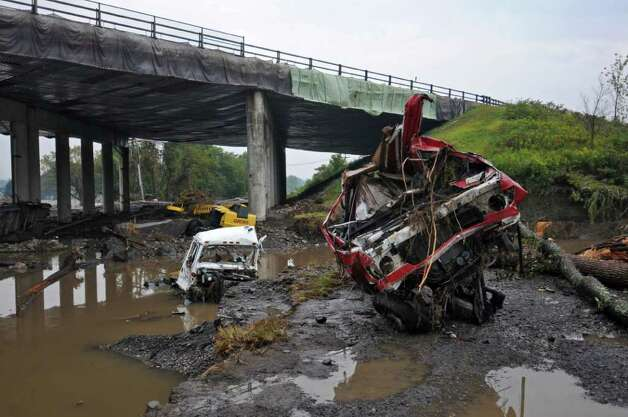 Route 5S was washed out by Tropical Storm Irene as it crosses underneath the NYS Thruway, as repair work continues on Thursday Sept. 1, 2011,  in the town of Amsterdam, NY. The truck at right was swept from Homestead Organics, a composting company located in an adjacent property. An office and other equipment were destroyed there, as well about 80-90 percent of  the year's compost, which sold at $32 per yard. Owner Ken Van Alstine, Sr. estimated that 1800-2000 yards of compost  were lost, and that the future of the business hangs in the balance, since he couldn't get flood insurance. He's hoping that FEMA will include Montgomery County in their plans to compensate people's losses. (Philip Kamrass / Times Union) Photo: Philip Kamrass / 10014489A