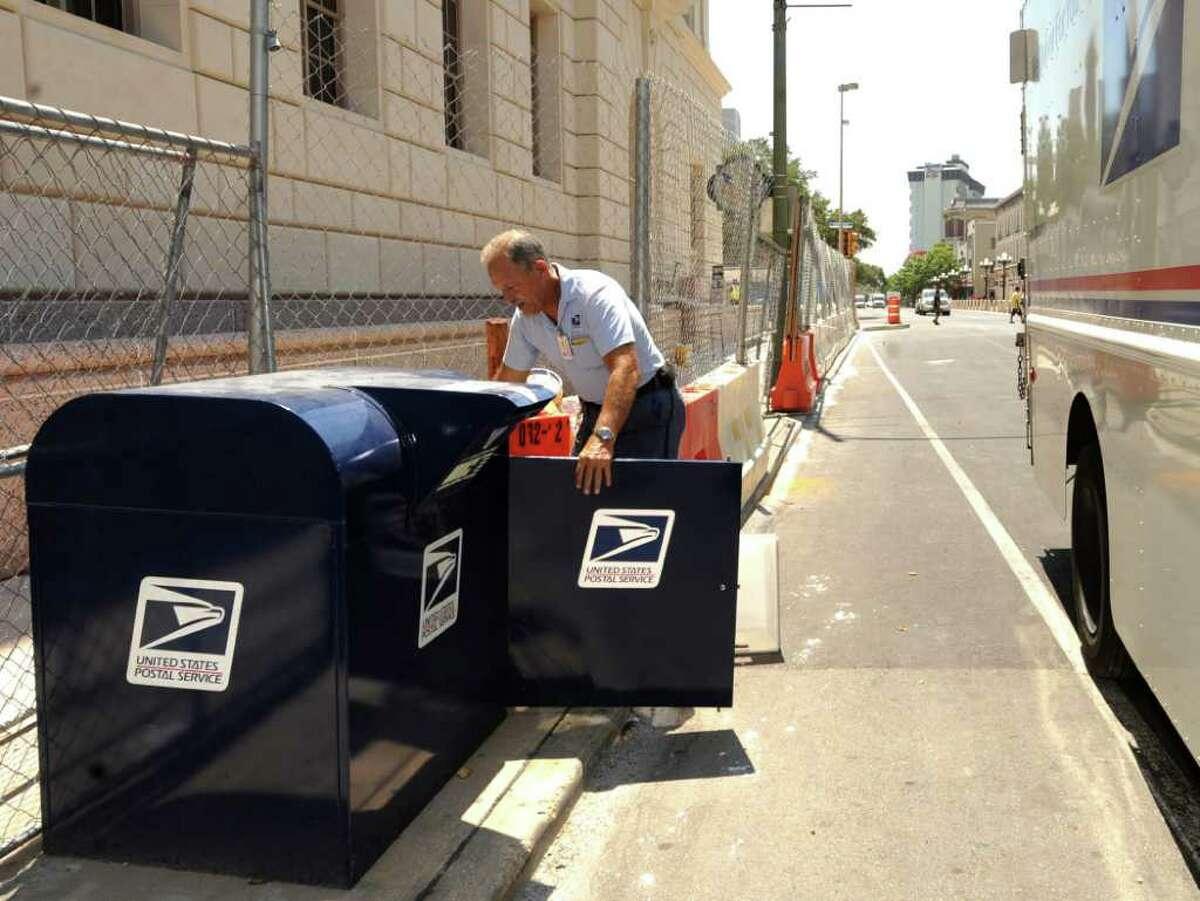 Postal Service mail collector David Prewitt gathers letters from a mailbox on Alamo Street near Houston Street.