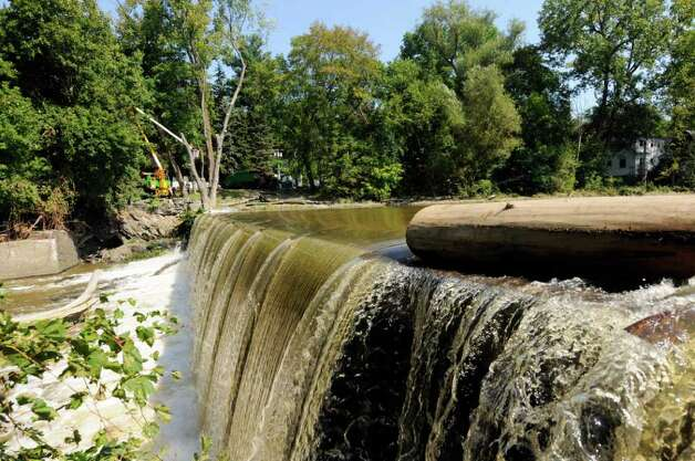 Water flows over the Poesten Kill Dam as crews work on the process of clearing a tree in Troy, NY, on Friday Sept.2, 2011.( Michael P. Farrell/Times Union) Photo: Michael P. Farrell