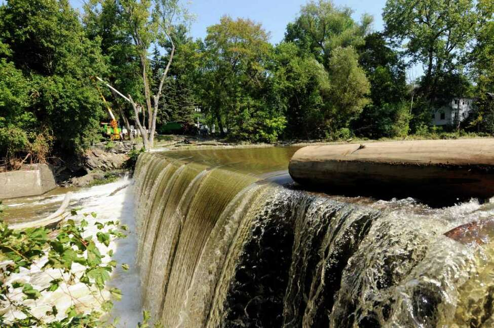 Water flows over the Poesten Kill Dam as crews work on the process of clearing a tree in Troy, NY, on Friday Sept.2, 2011.( Michael P. Farrell/Times Union)