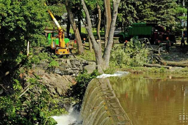 Water flows over the Poestenkill Dam as crews work on the process of clearing a tree in Troy, NYFriday Sept.2, 2011.( Michael P. Farrell/Times Union) Photo: Michael P. Farrell