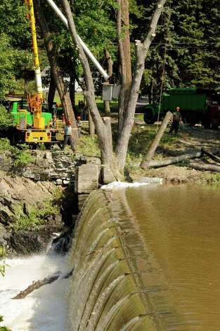 Water flows over the Poesten Kill Dam as crews work on the process of clearing a tree in Troy, NY, on Friday, Sept.2, 2011.( Michael P. Farrell/Times Union) Photo: Michael P. Farrell