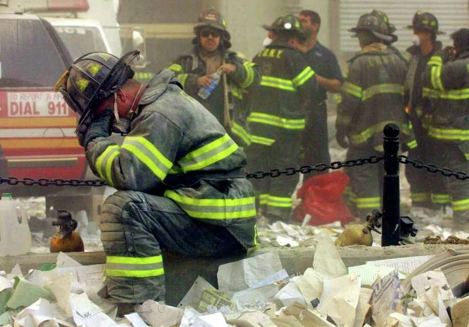 A firefighter breaks down after the World Trade Center buildings collapsed September 11, 2001 after two hijacked airplanes slammed into the twin towers in a terrorist attack. Photo: Mario Tama, Getty Images / (?) Copyright 2001 by Getty Images