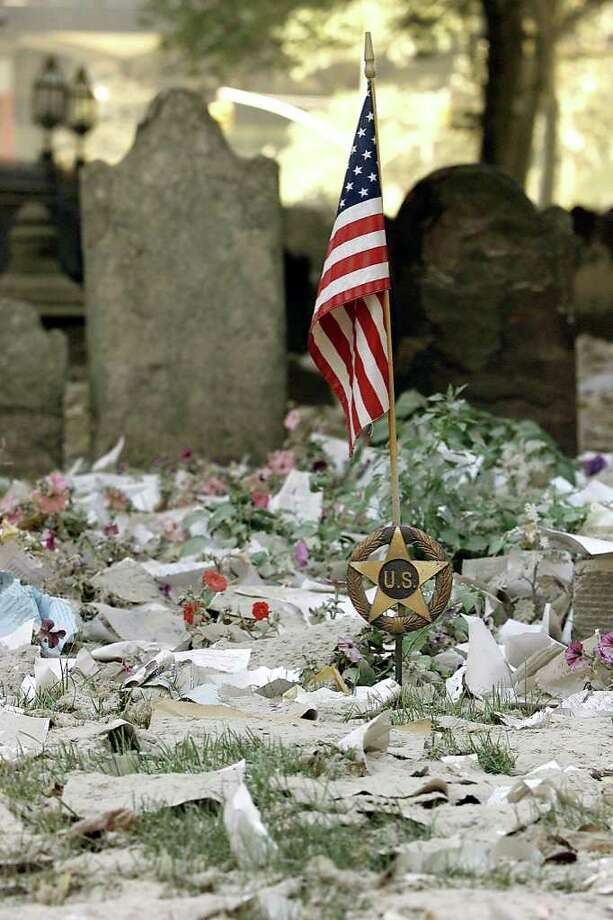 An US flag is seen amidst debris in the cemetery at Trinity Church next to the World Trade Center 13 September, 2001 in New York. The twin towers at the center were destroyed 11 September when hijacked airplanes crashed into the towers.  Photo: BETH A. KEISER, AFP/Getty Images / 2011 AFP