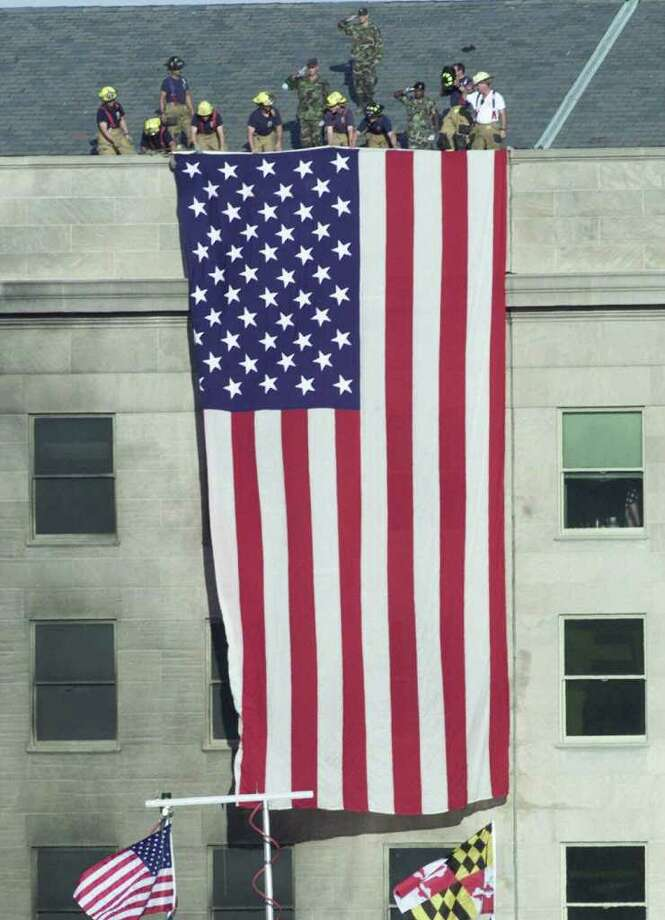 Firefighters unfurl an American flag from the roof of the Pentagon Wednesday, Sept. 12, 2001, as President Bush visits the area of the Pentagon where an airliner, hijacked by terrorists, crashed into the building on Tuesday. Photo: AP