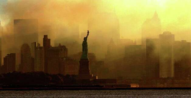 The Statue of Liberty is seen at first light in this view from Jersey City, N.J., against a smoke-filled backdrop of the lower Manhattan skyline, early Saturday, Sept. 15, 2001. Photo: AP / SL