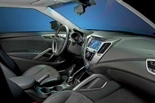 There are sporty bucket seats and metallic trim in the cockpit of the Veloster, along with a standard 7-inch touch-screen color display in the dash. COURTESY OF HYUNDAI MOTOR AMERICA Photo: Hyundai Motor America, COURTESY OF HYUNDAI MOTOR AMERICA