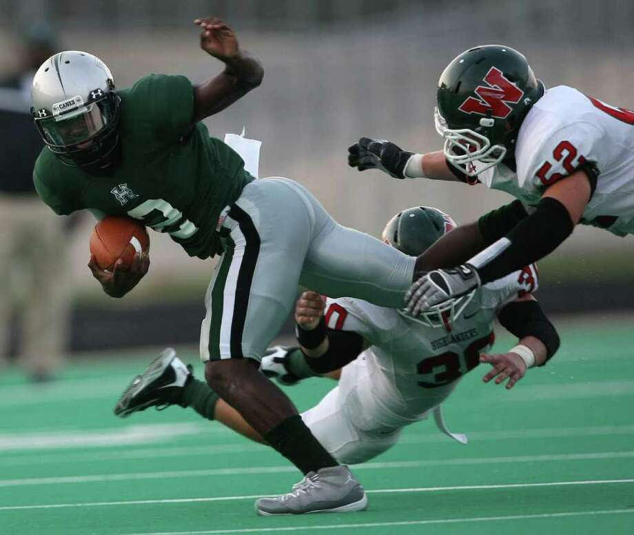 Hightower's Bralon Addison (2) avoids a sack by The Woodlands' Mike Ciaramitaro (30) and Brandon Taylor (52)during the first half of their game, Friday at Hall Stadium in Missouri City. Photo: Eric Christian Smith, For The Chronicle