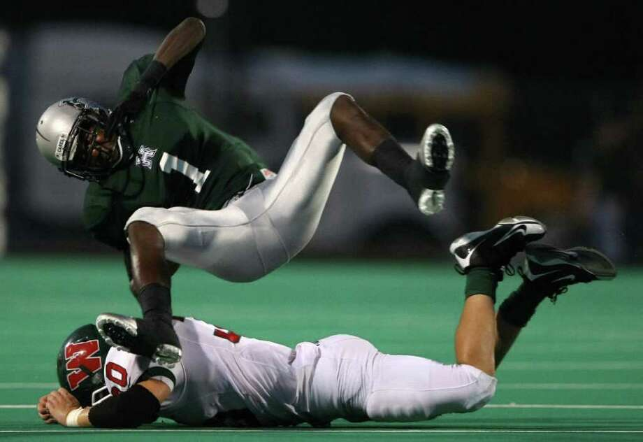 Huightower's Ryan Nelson (1) flips over The Woodlands' Mike Ciaramitaro after a reception during the first half of their game, Friday at Hall Stadium in Missouri City. Photo: Eric Christian Smith, For The Chronicle