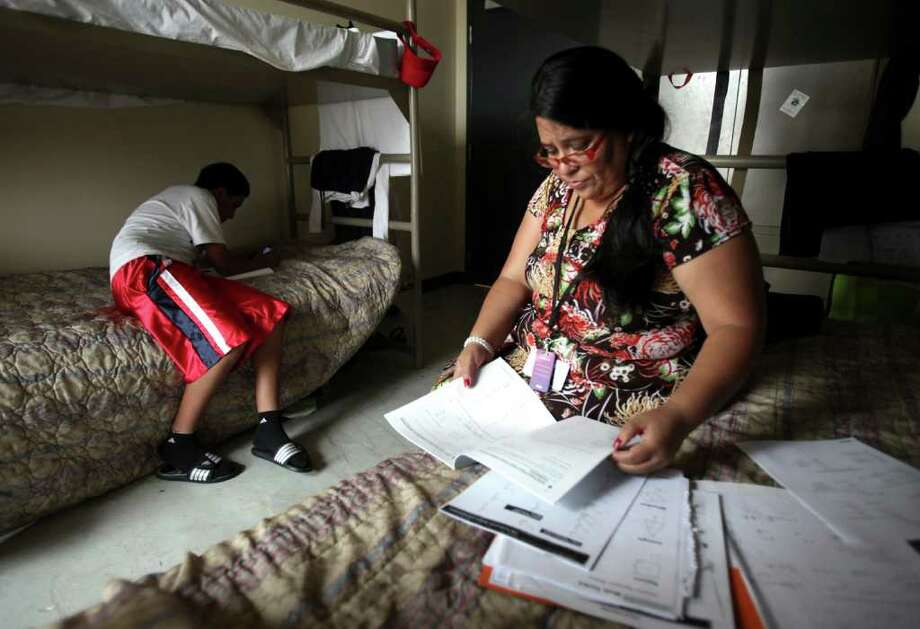 Metro daily - Emma Gutierrez, right, studies her homework as her son Uriel Hernandez, 13, sketches in their room at Haven for Hope.  Friday, July 29, 2011. Photo Bob Owen/rowen@express-news.net Photo: Bob Owen, Bob Owen/rowen@express-news.net / rowen@express-news.net
