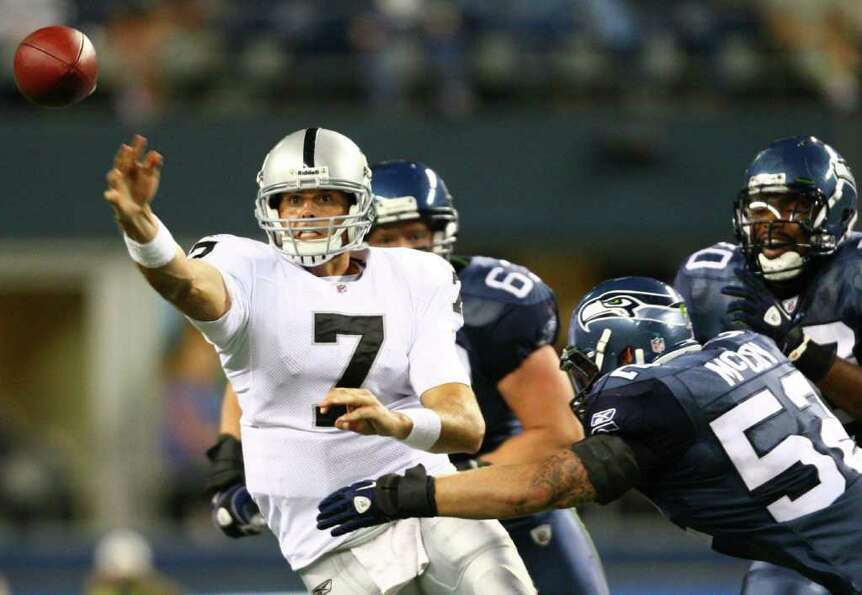 Oakland Raiders quarterback Kyle Boller releases the ball under pressure from Seattle Seahawks playe
