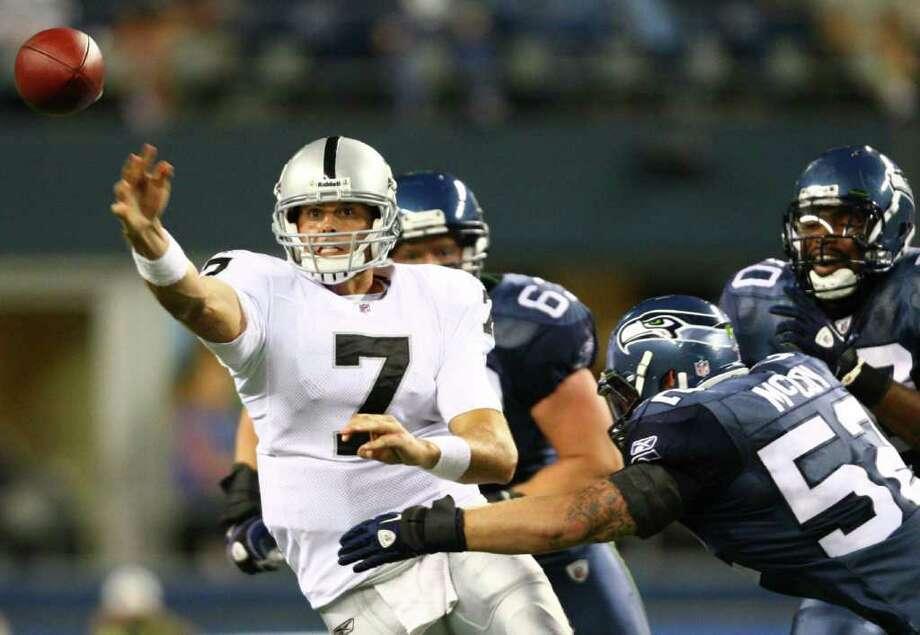 Oakland Raiders quarterback Kyle Boller releases the ball under pressure from Seattle Seahawks player Matt McCoy. Photo: JOSHUA TRUJILLO / SEATTLEPI.COM