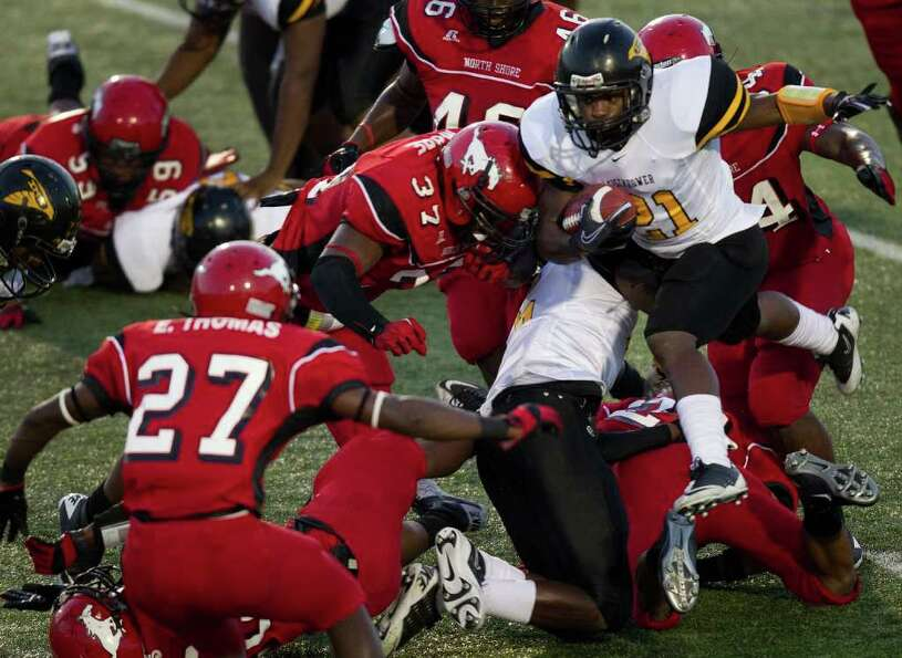 Eisenhower running back Brian Heard (21) finds little room to run in the North Shore defense during