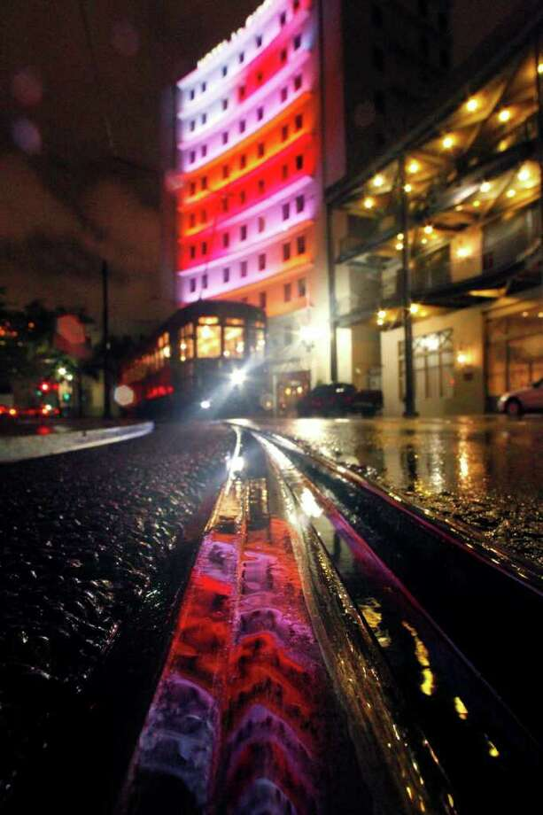 A hotel is reflected in puddles from rain from approaching Tropical Storm Lee on a streetcar track, as a streetcar passes through Lee Circle in New Orleans, Friday, Sept. 2, 2011. Lee formed in the waters off Louisiana on Friday, threatening a drenching along much of the Gulf coast over the Labor Day weekend with up to 20 inches (50 centimeters) of rain in some spots. (AP Photo/Gerald Herbert) Photo: Gerald Herbert, STF / AP