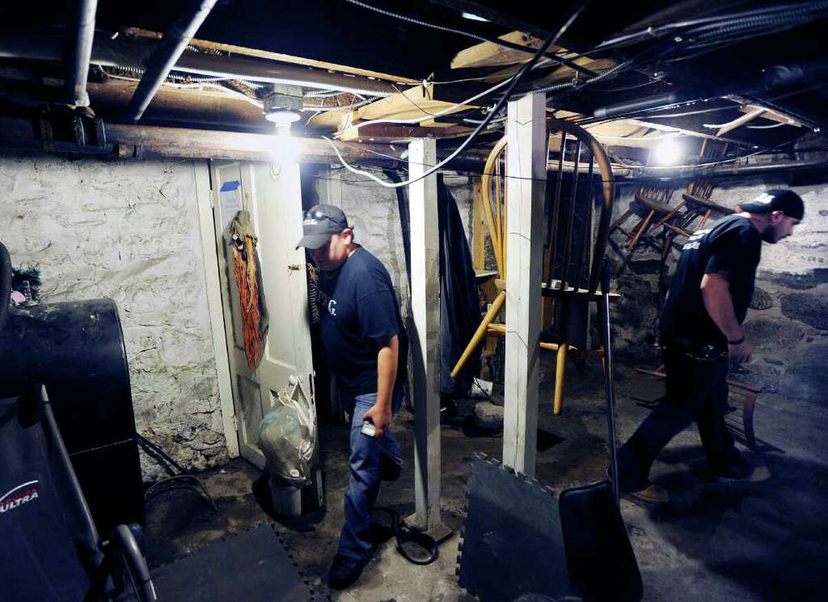 """Todd Harrington, left, and Dave Rudolf, right, both of the Norwalk Paranormal Research Group, search for spirits in the basement of the Stamford home owned Melissa Leigh, Friday night, Sept. 2, 2011. Leigh said she feels the presence of her deceased father, Frederick Leigh, in the house that was owned at one time by Vivian Vance who was best known for her role as Ethel Mertz on the television sitcom """"I Love Lucy."""""""