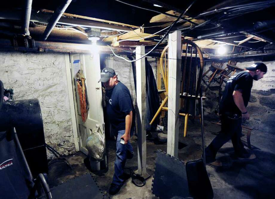 "Todd Harrington, left, and Dave Rudolf, right, both of the Norwalk Paranormal Research Group, search for spirits in the basement of the Stamford home owned Melissa Leigh, Friday night, Sept. 2, 2011.  Leigh said she feels the presence of her deceased father, Frederick Leigh, in the house that was owned at one time by Vivian Vance who was best known for her role as Ethel Mertz on the television sitcom ""I Love Lucy."" Photo: Bob Luckey / Greenwich Time"