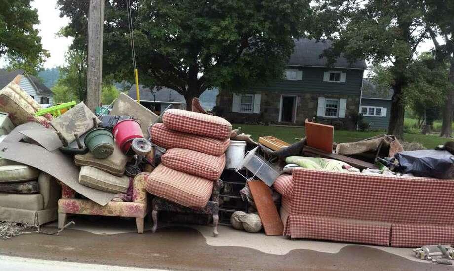 STEVE BARNES/TIMES UNION  Flood-ruined household belongings line Main Street in the village of Schoharie on Saturday, Sept. 3, 2011.