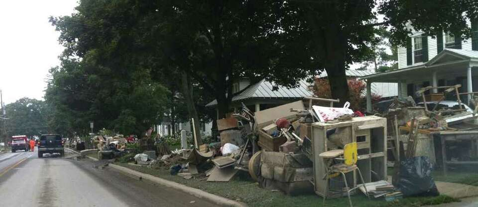 STEVE BARNES/TIMES UNION  Flood-ruined household belongings line Main Street in the village of Sch