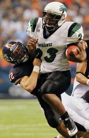 Northeastern State's Travis Evans, right, is brought down by UTSA's Nic Johnston during the first half of an NCAA college football game, Saturday, Sept. 3, 2011, at the Alamodome in San Antonio. (AP Photo/Darren Abate) Photo: Express-News