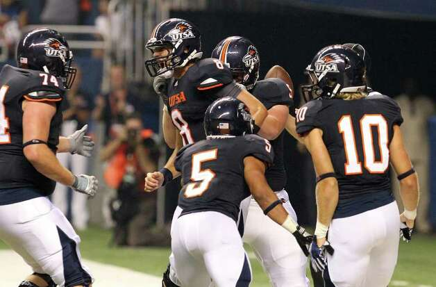 UTSA quarterback Eric Soza (center) gets congratulated by teammates after scoring the team's first touchdown against Northeastern State in the first quarter at the Alamodome on Saturday, Sept. 3, 2011. Kin Man Hui/kmhui@express-news.net Photo: Kin Man Hui, Express-News / SAN ANTONIO EXPRESS-NEWS (NFS)